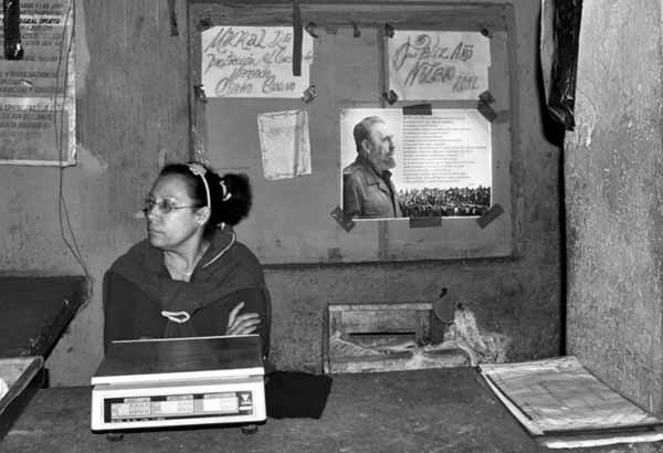 Photo of woman in Cuba market with poster of Fidel Castro in background. Copyright 2015 by Pac McLaurin